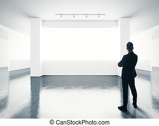 Business man looking at empty screen in contemporary gallery.