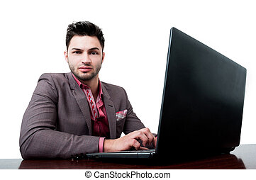Business man looking at the camera while working on his laptop