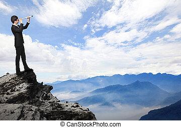business man looks through telescope on mountain