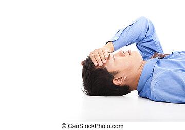 business man lying on floor with headache