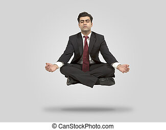 Business man meditates in mid air