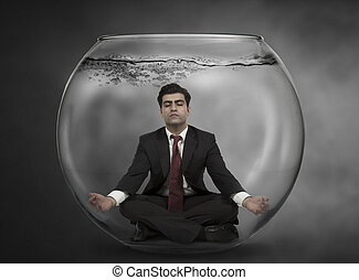 Business man meditates under water in a fish bowl
