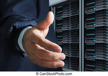 business man offers handshake in server room