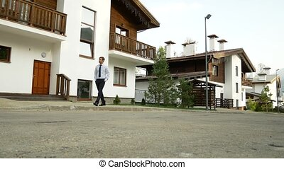 business man on a background of a chalet, a house in the mountains. 4k. enjoys the view of nature
