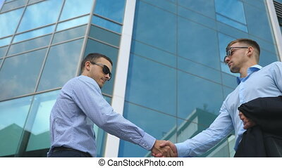 Business man passing a black briefcase to his partner. Colleagues shake hands outdoor in the city background. Two young businessmen meeting near office and greeting each other. Close up Slow motion
