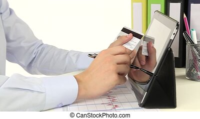 Business man paying with credit card by tablet.