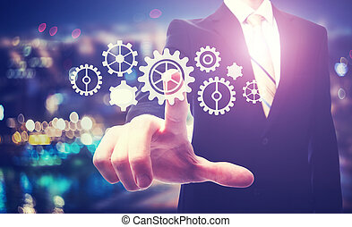 Business man pointing to gears on a blurred city background