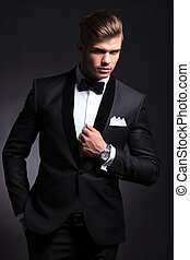 business man poses in tuxedo - elegant young fashion man in...