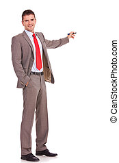 handsome young business man presenting something in the back with a pen and holding a hand in his pocket while looking at the camera on white background