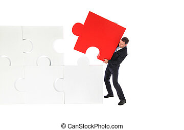 Business man pushing the final piece of puzzle