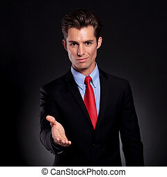 business man puts out hand - portrait of a young business...