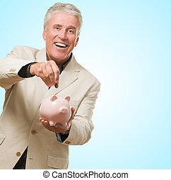 Business Man Putting Money In Piggy Bank