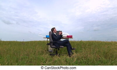 Business man relaxing at desk in virtual office under open...