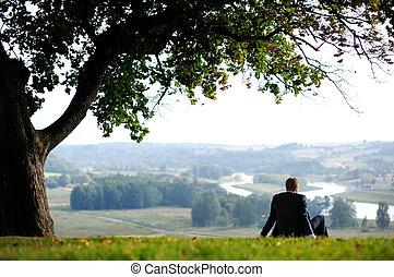 Business man resting under an giant oak