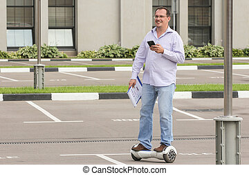 Business man riding an electronic scooter outdoors