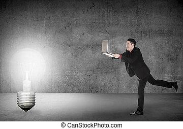 Business man run with laptop chasing light bulb. Making idea...
