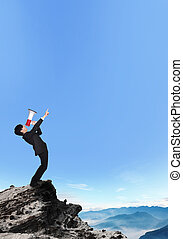 business man shouting into a megaphone and finger point to copy space on a mountain, asian model