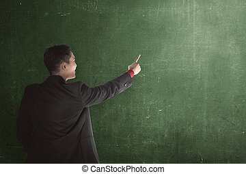 Business man show something with chalkboard background