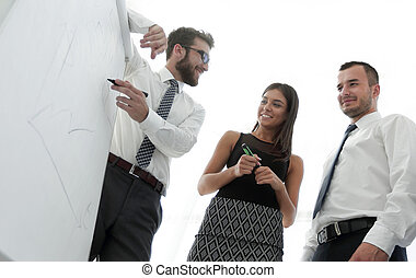 business man showing something on a whiteboard to his colleagues