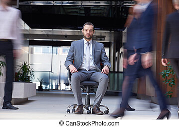 business man sitting in office chair, people group  passing by