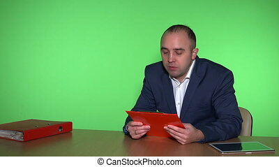 Business man sitting in office with clipboard and consulting customer