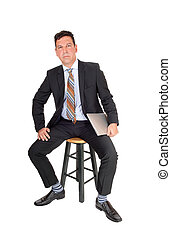 Business man sitting with laptop in hand