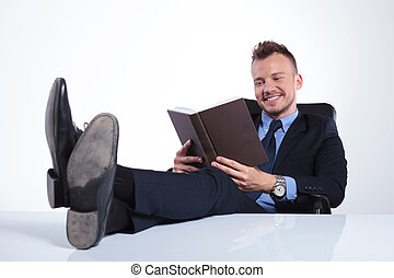 business man smiles while reading