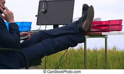 Business man speaks by mobile phone while sitting at office desk in a green field