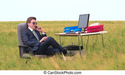 Business man speaks by phone sitting at a desk in wheat field