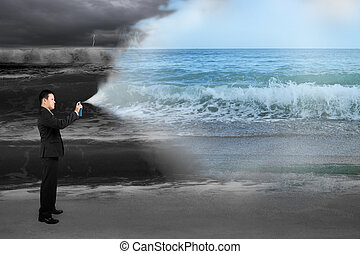 Business man spraying calm sea paint covered dark stormy ocean