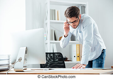 Business man standing at desk working on documents with mobilephone