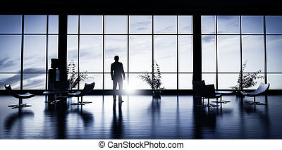 Business man standing in the office looking out of the...