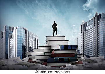 Business man standing on the top of books