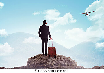 Business man standing on the top of the mountain