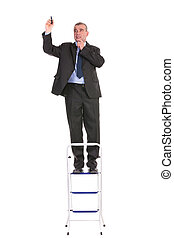 business man stands on ladder and writes