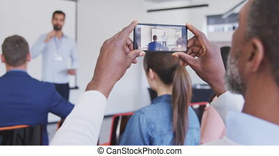 Business man taking videos of meeting in conference room - ...
