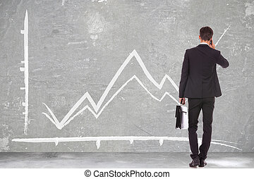 business man talking on phone in front of graph