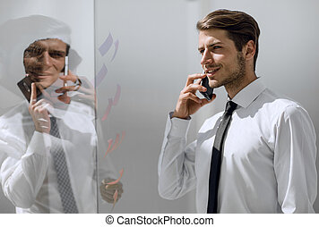 business man talking on smartphone in office.