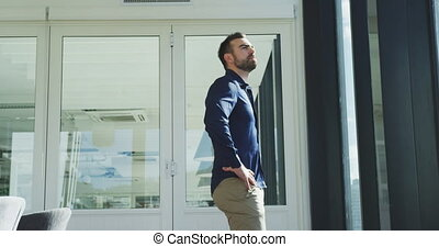Side view of a Caucasian businessman working in a modern office, taking a break standing by the window with hands on hips admiring the view in slow motion