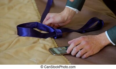 Business Man Tying a Tie with Manual in Phone