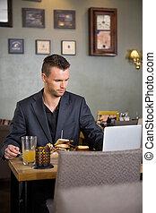 Business Man Using Laptop While Having Sandwich