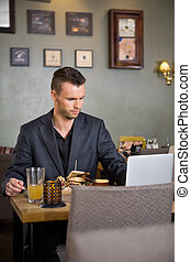 Business Man Using Laptop While Having Sandwich