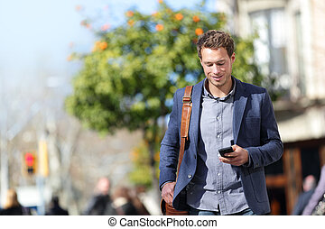 Business man using mobile phone walking to work. Young urban...
