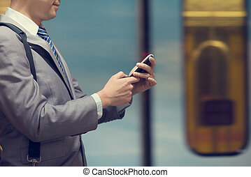 Business man using smart phone at train station.