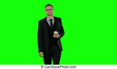 Business man walking and drinking cup of coffee. Green screen.