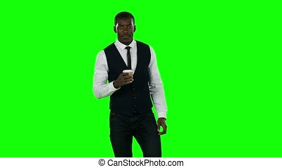 Business man walking and drinking coffee. Green screen.