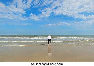 Business man walking in the sea