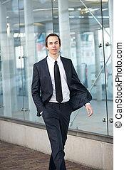 Business man walking on sidewalk in the city