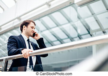 Business man walking while talking on mobile phone on his way to work