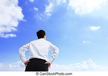 Business man watching the sky with copy space